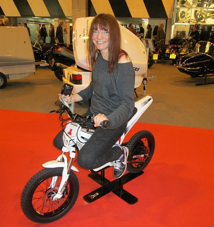 Sharon sits smiling on a tiny kids electric off road motorcycle