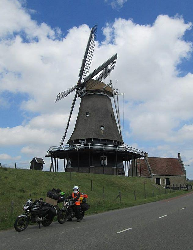Sharon on her bike beneath a large Dutch windmill