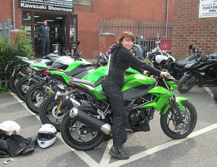 Sharon is smiling as she sits on the new Z250SL outside the shop