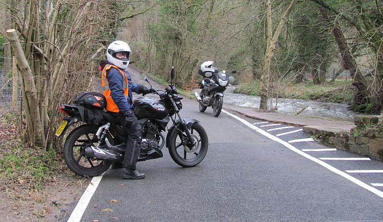 Sharon on her 125 down a narrow lane with a deep ford