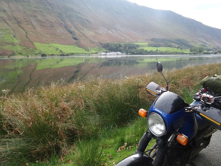 Looking across a broad lake to a steep mountainside with the bike in the front of the shot