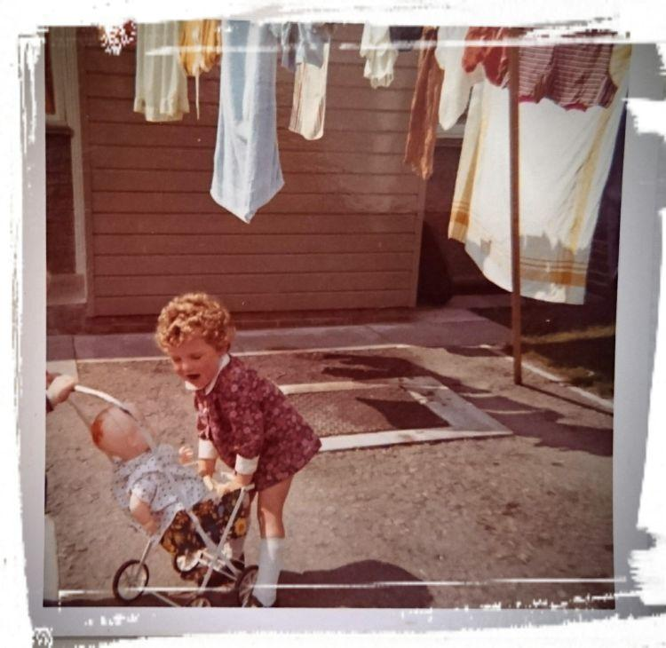 Toddler Sharon grabbing a toy pram in an old colour photo