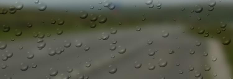 A very blurred stretch of road with rain drops over the whole image