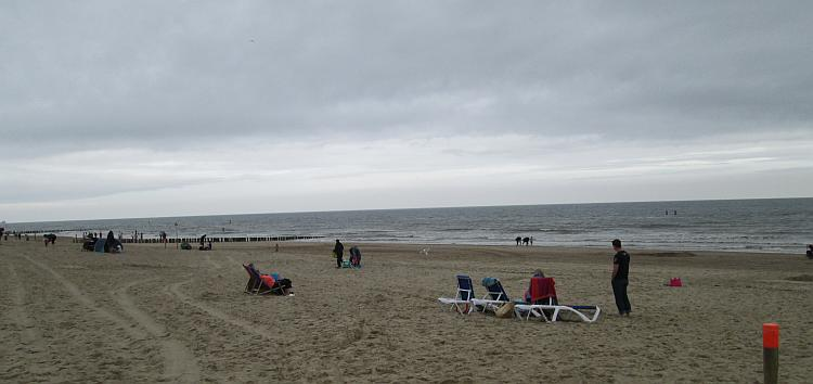 A sandy beach with a sprinking of holiday makers, but the skies are grey
