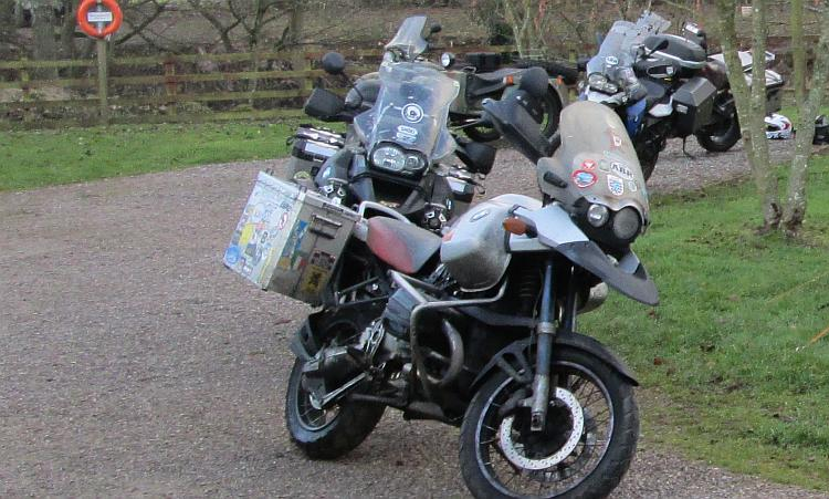 Several large BMW GS adventure bikes at a campsite