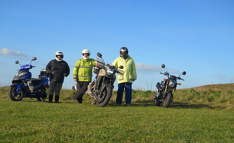 Mark Nina and Ren stand beside their motorcycles at Godrevy