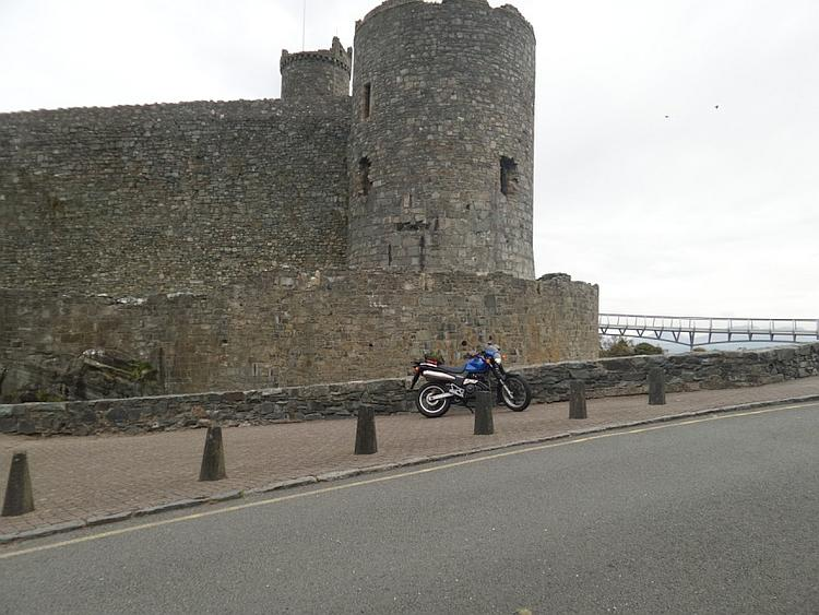 The bright blue 650 outside the massive walls of Harlech castle