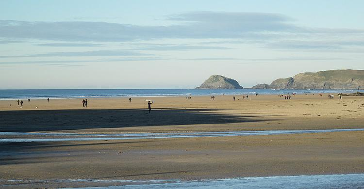 Perranporth beach is broad flat sandy beach. There is a number of people about but not too busy