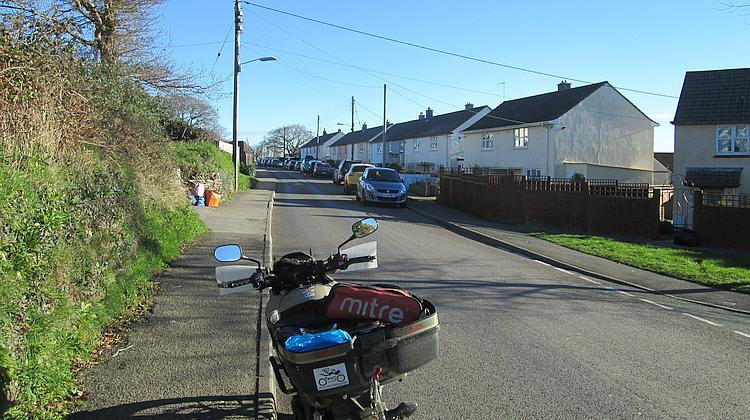 An ordinary street with houses, telephone poles, parked cars and hedges in St Austell