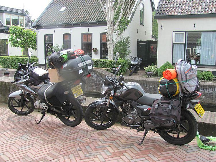 The 2 overladen 125 motorcycles with luggage beside the canal on the way to Amsterdam