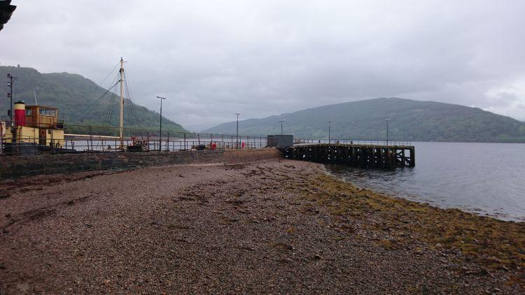 A wooden and stone jetty juts out into a misty Highland lock with a boat behind the wall
