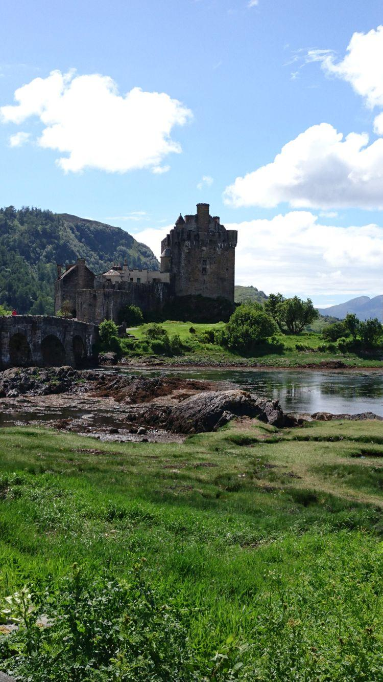 The Eilean Donan castle bathed in sun. The castle is on an island into the loch