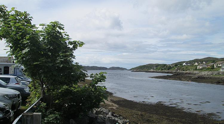 Loch Inver seen from Lochinver town. A small town sloping down to the sea loch