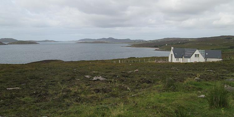 A modern highland house painted traditionally white, all alone set against a broad sea loch