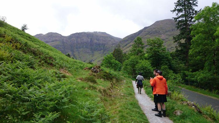 3 men walking through Glencoe looking for hagrids hut. One is wearing a black skirt