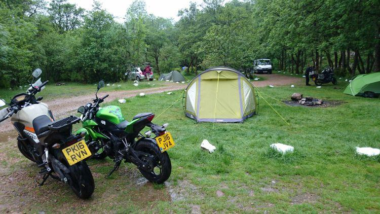 The motorcycles are at the wet and tree filled campsite as the tent is put up