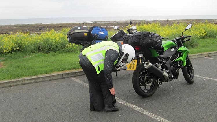 Sharon's zipper up her waterproof pants in a car park on the Ayrshire coast