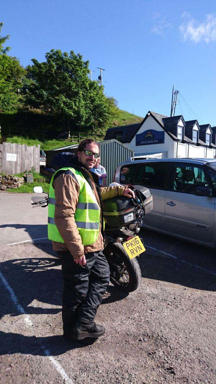 Ren stands next to his 500 smiling in the sun at the Applecross Pub