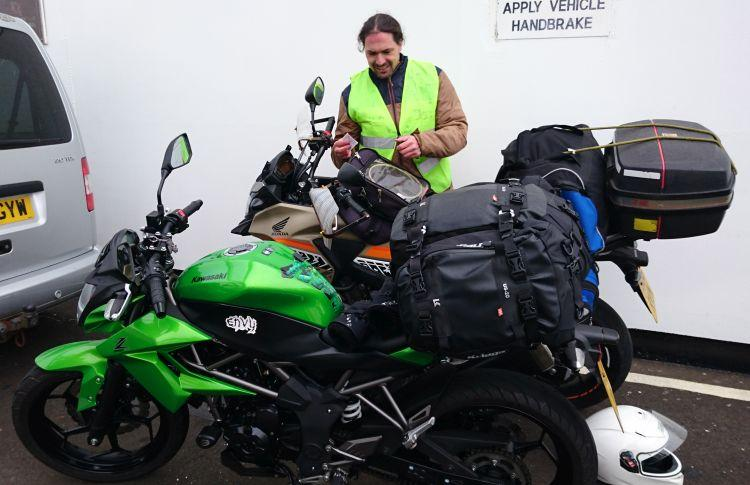 Ren's poking around in his tank bag with a sign behind him stating apply vehicle handbrake