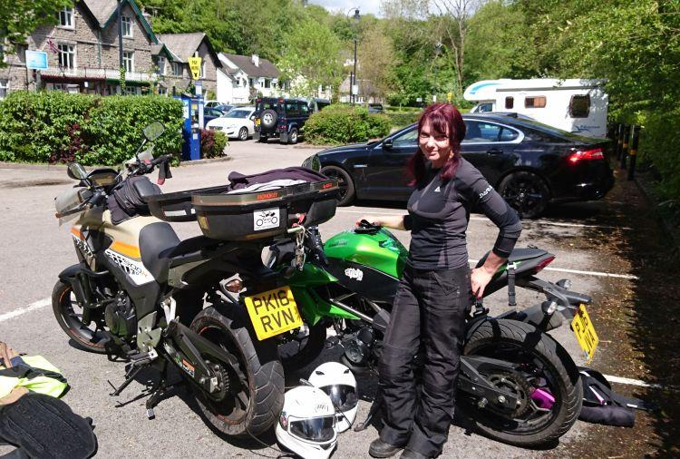 Sharon poses in the sun next to her motorcycle in the picturesque surroundings of Grange Over Sands