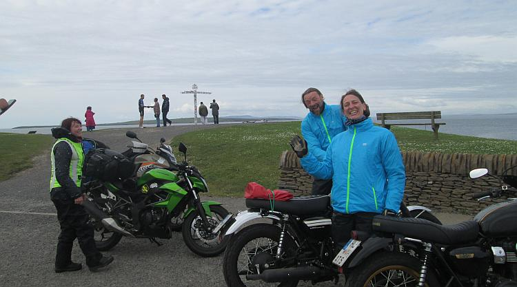 2 people in bright blue waterproofs at John O'Groats