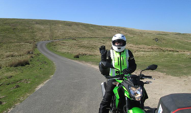 Sharon sits on her bike in all her gear waving at the camera surrounded by beautiful folling hills