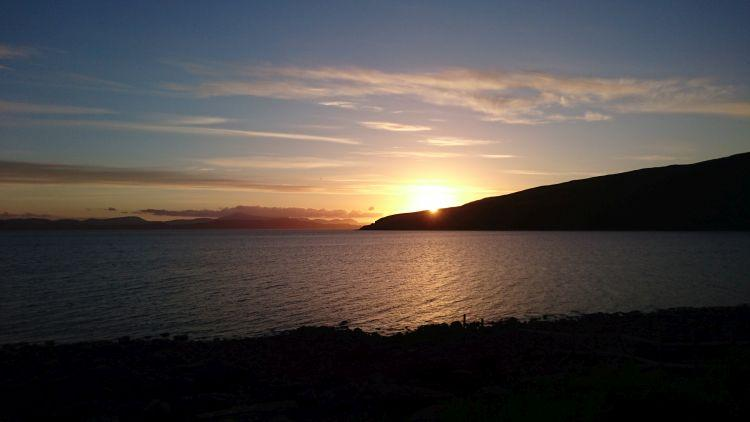 The sun set over a peninsula from the sea wall at Applecross. Deep red sunset