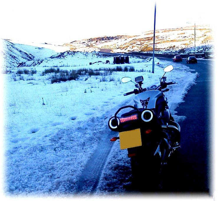 Tom's MT01 parked at the side of a lane passing through snowy hills and mountains