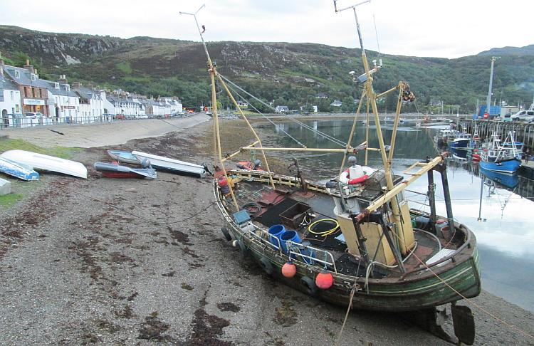 A boat on the shoreline, tha harbour and houses of Ullapool