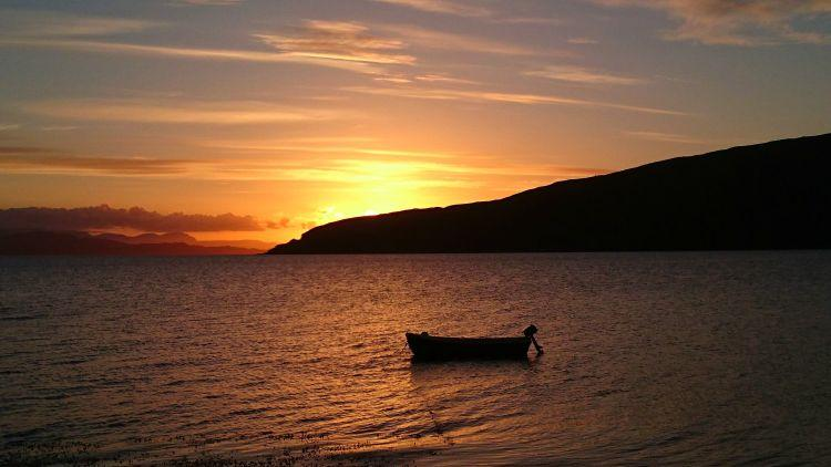 a small boat with outboard motor on the still waters near applecross as the sun sets deep orange