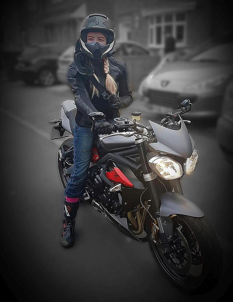 Jade sat on her Triumph Street Triple smiling with her helmet on