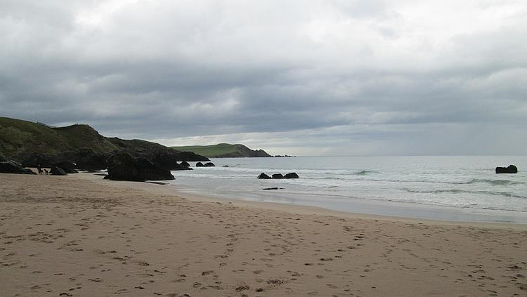 Rugged rock lead down to a sandy beach in the rain at Durness