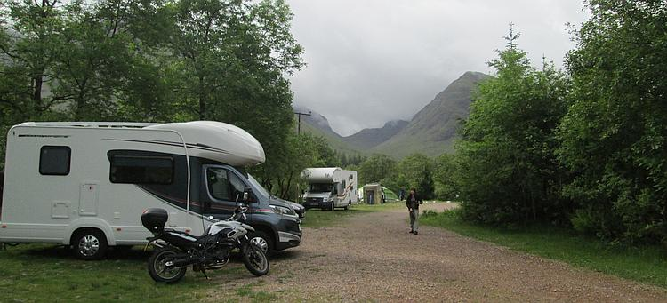 A campervan and motorcycles set against the dramatic and steep hillsides of the Glencoe valley