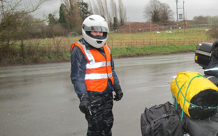 Sharon standing in all her wet weather riding gear looking wryly at the camera