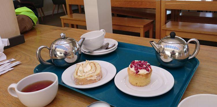 2 bright chrome tea pots, cups, saucers and sweet cakes on the table at Tebay services
