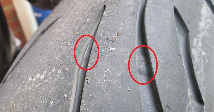 The tread wear indicators in a tyre tread circled in red